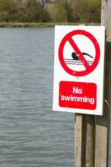 No swimming sign at edge of lake