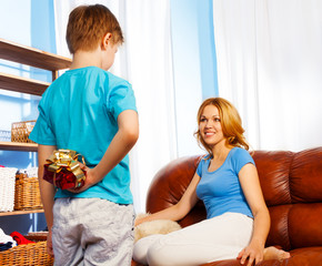 Boy holding the gift behind to surprise mother
