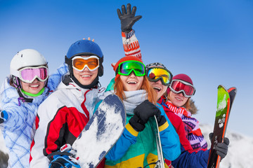 Positive friends with snowboards and skis