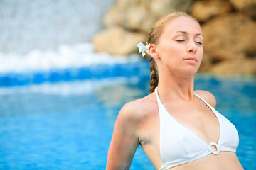 Young woman relaxing in the swimming pool at Spa center