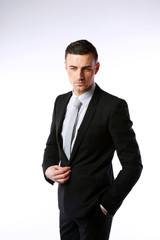 Pensive businessman buttoning his jacket on a gray background