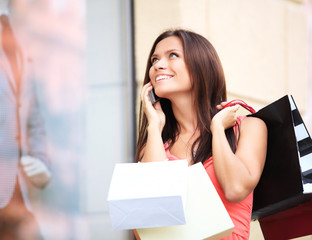 Happy woman holding shopping bags and using cell phone