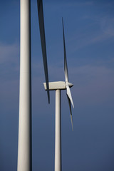 Two wind turbines against blue sky
