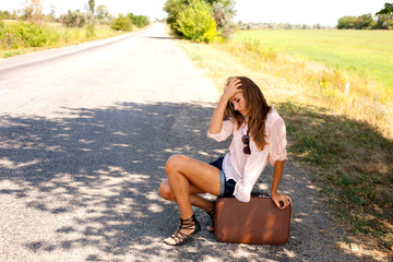 Desperate woman sitting on a suitcase by a countryside road