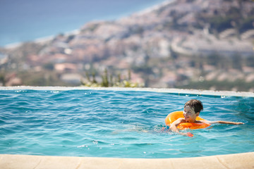 Little boy with swimtrainer in swimming pool
