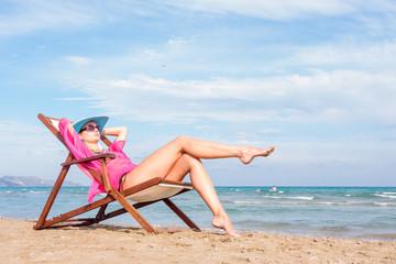 Girl sitting on a chair on the beach