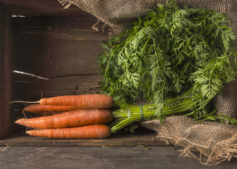carrots bunch with leaves in old wooden box