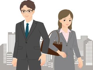 都市のビル群とスーツの男女