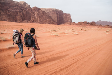 Two young girl are walking across desert of Wadi Rum in Jordan