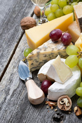 assortment of fresh cheeses, grapes and walnuts on wooden table