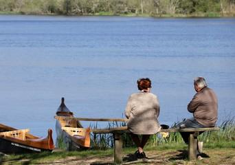 couples de personnes agées sur un banc face au lac