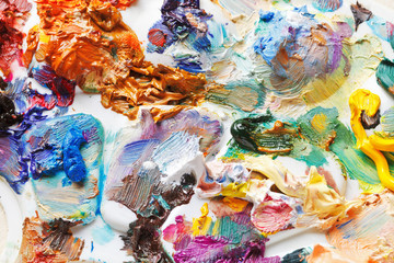 strokes of oil paints on palette close up