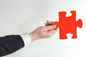 red puzzle piece in male hand