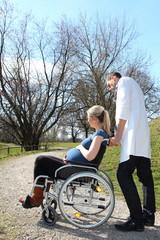 Arzt mit schwangeren Rollstuhlfahrerin im Park