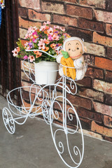 White bicycle carrying flowers with brown wall