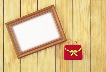 Frame and gift box on the background of  wooden laths