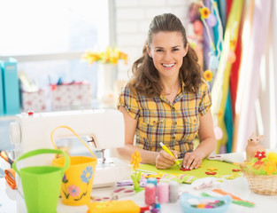 Happy young woman making easter decoration
