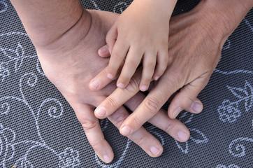 Drei Haende einer Familie uebereinander auf grauemTisch