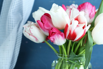 Beautiful tulips in glass jug on color wooden background