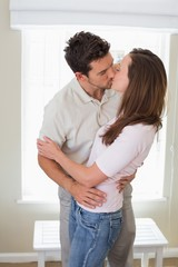 Loving young couple kissing at home