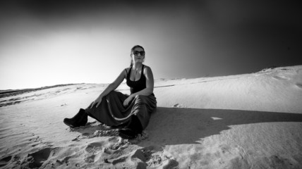 photo of tired woman sitting on sand dune