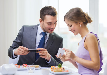 smiling couple with sushi and smartphones