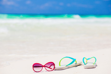 flip flops and sunglasses on tropical beach with waves on