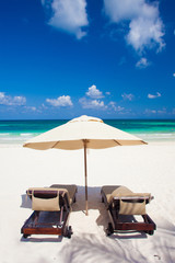 two beach chairs and umbrella on white sand beach. Holidays