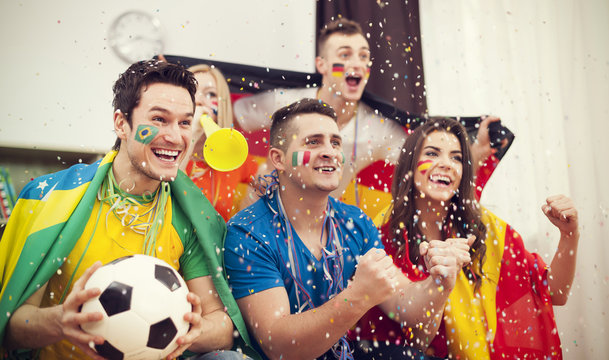 Multinational football supporters celebrating goal