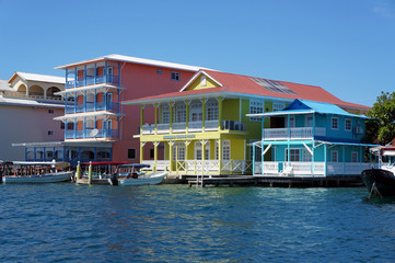 Colorful Caribbean houses over water with boats