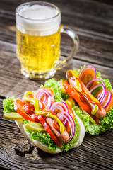 Fresh hot dog with sausage and vegetables and beer