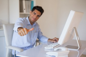 Casual businessman giving thumbs up to camera at his desk