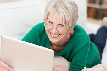 moderne seniorin liegt mit laptop auf dem sofa