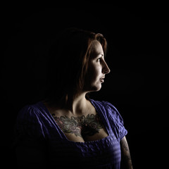 beautiful woman with tattoo in black background