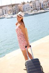 Beautiful fancy girl pulling suitcase on marina