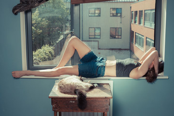 Young woman lying in window