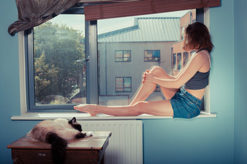 Young woman on window sill with cat