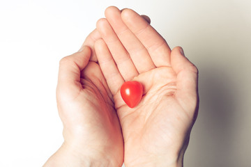 Hands holding heart shaped tomato
