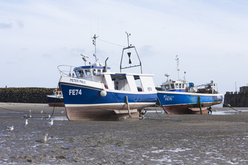 Two blue boats at Folkestone harbour at low tide, Kent, UK