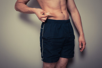 Fit young man pinching his stomach