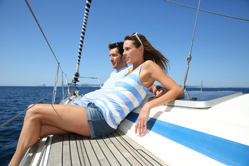 Cheerful couple relaxing on sailboat while navigating