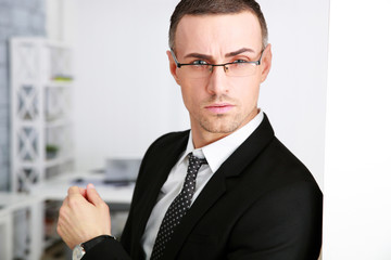 Portrait of a confident businessman in glasses at office