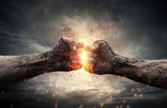 Fight, two fists hitting each other over dramatic sky