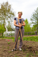 Cheerful smiling blonde with a shovel and rake in the garden