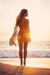 Beautiful surfer girl on the beach at sunset