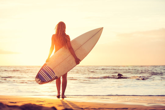 Surfer girl on the beach at sunset