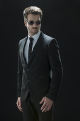 handsome man in black suit on a black background
