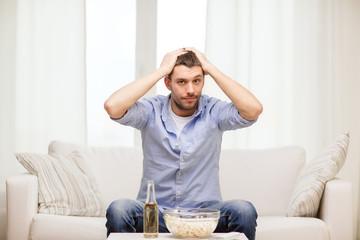 sad man watching sports at home