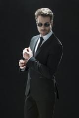 handsome man in black suit on a black background