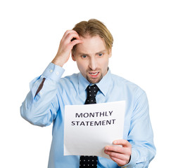 Expensive bills. Man surprised, unhappy about monthly statement